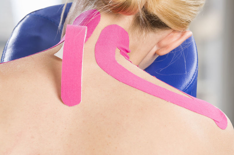 Rear view of mature woman with pink kinesio tape on back