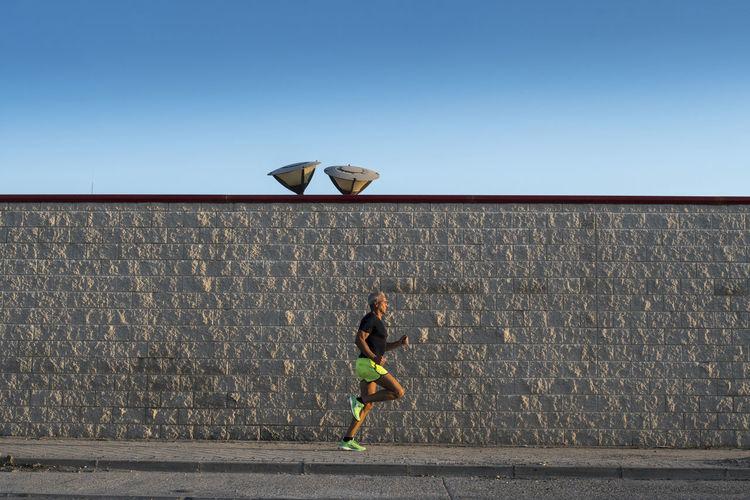 Full length of man running on wall against sky