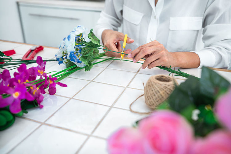 Midsection of woman holding flowers on table
