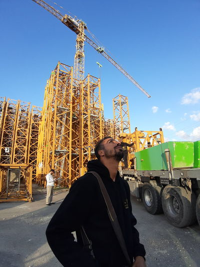 Man standing at construction site against sky