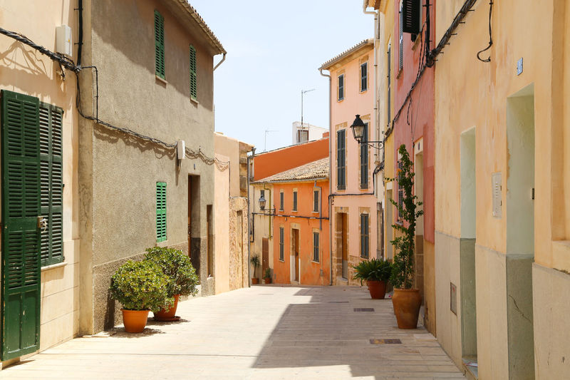 Mallorca SPAIN Spanish Town Alley Apartment Building Architecture Building Exterior Built Structure Day Facades Full Frame Full Length No People Outdoors Pastel Colored Pastel Colors Picturesque Plant Spanish Arquitecture Stone Houses  Street Streetview