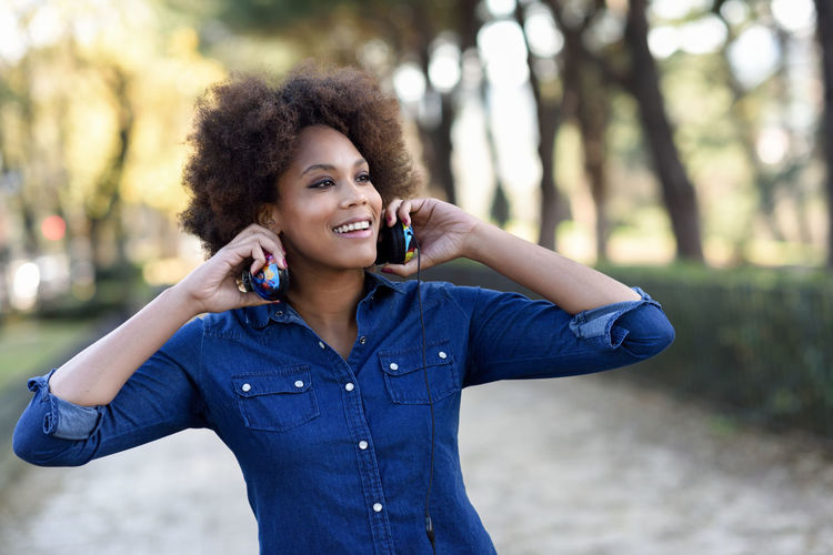 Smiling Young Woman Holding Headphones While Standing At Public Park