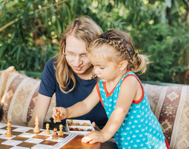 Father playing chess with cute daughter in yard