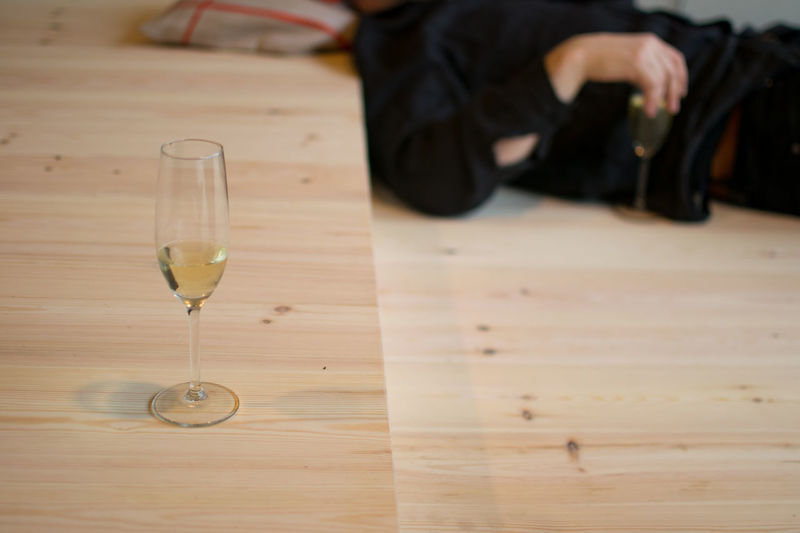 Champagne Flute By Man Lying On Floor
