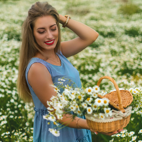 Beautiful young woman holding basket while standing against wall