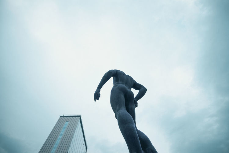 Low angle view of person sculpture against sky