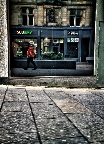 Rear view of woman walking on footpath by building