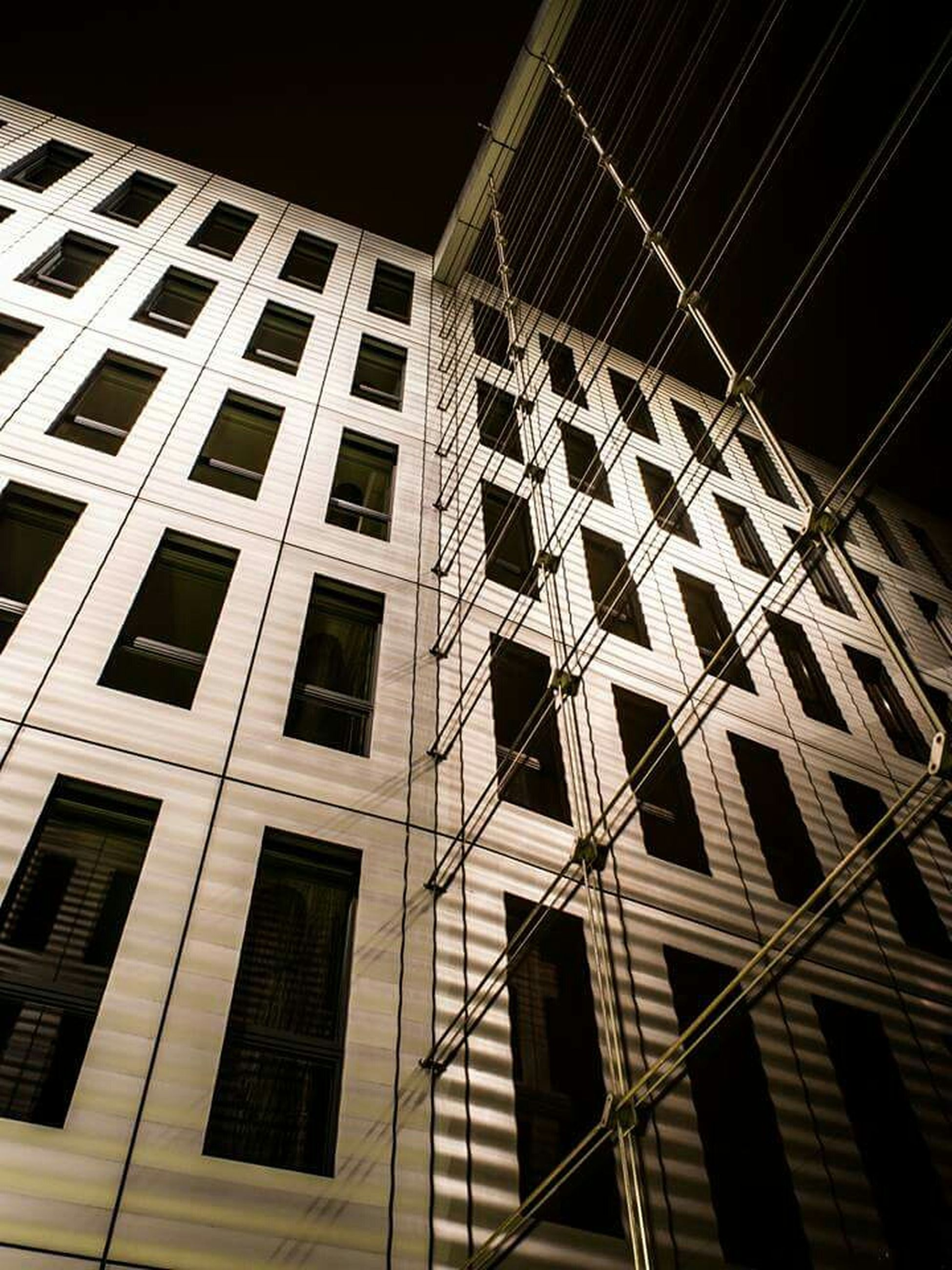 low angle view, architecture, built structure, building exterior, window, building, pattern, night, modern, repetition, architectural feature, glass - material, no people, indoors, design, geometric shape, city, office building