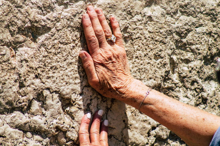 Close-up of person hand on rock