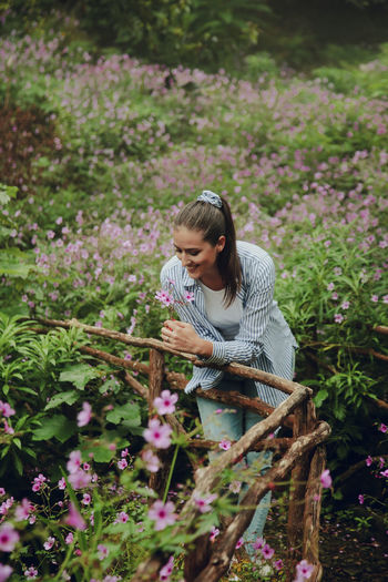 Adorable brunette in a rain forest with a flowers all around