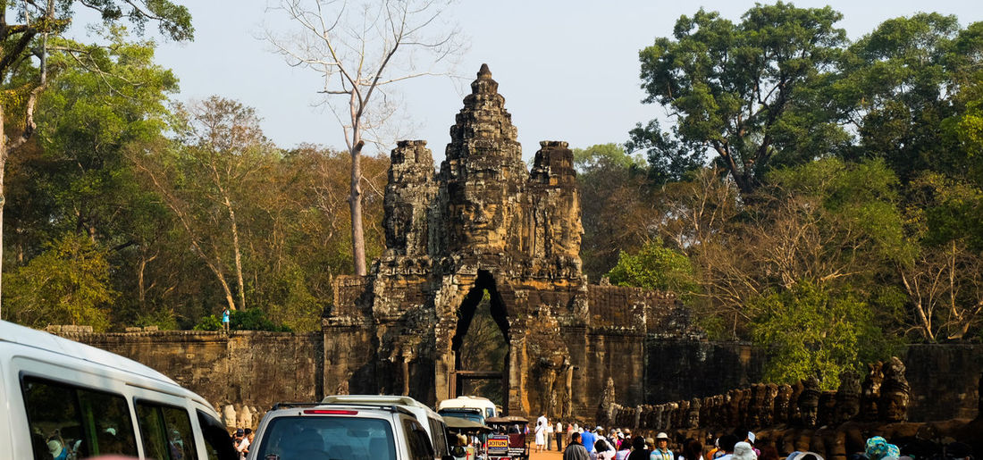 Angkor Thom Gate in Siemriep Cambodia Tree Religion Large Group Of People Built Structure Architecture Place Of Worship Spirituality Outdoors Travel Destinations Sculpture Statue Day Sky Nature People Culture Heritage Angkor Thom Angkorarcheologicalpark Architecture Landscape Gate Cambodia Photography Archaeology Tourism