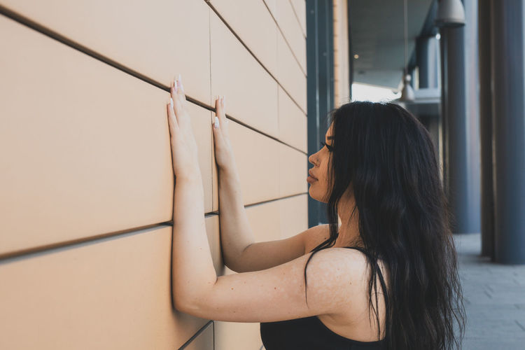 Side view of young woman touching wall while standing outdoors