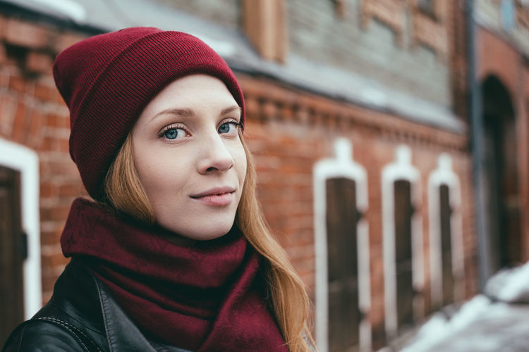 Portrait of beautiful young woman wearing knit hat and scarf outdoors