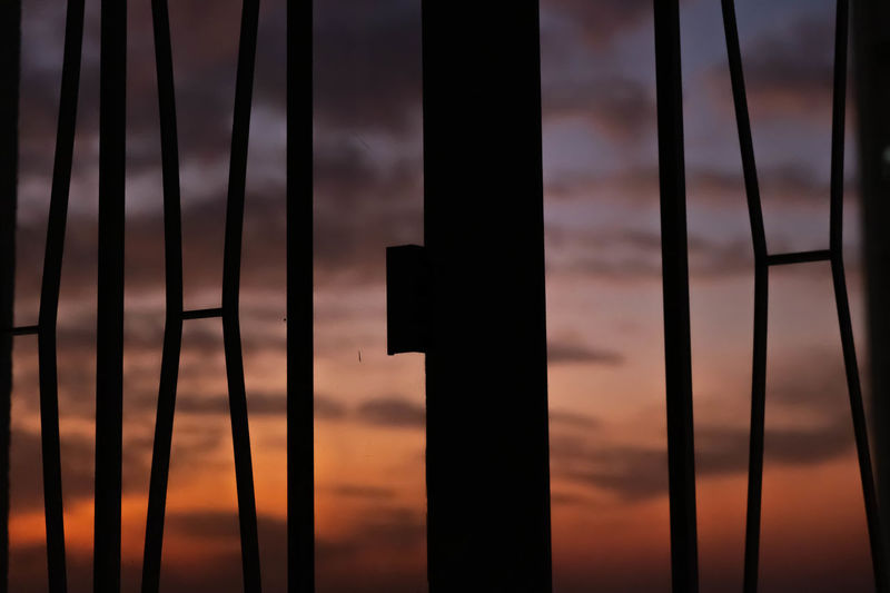 Close-up of silhouette fence against sky during sunset