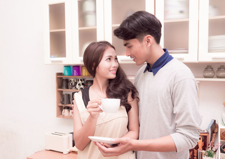 Asian couple drinking coffee in the kitchen Asian  Beautiful Breakfast Casual Coffee Cooking Couple Family Happiness Husband Love Relationship Cheerful Drinking Female Food Girl Hobby Kitchen Male Model People Smile Together Wife