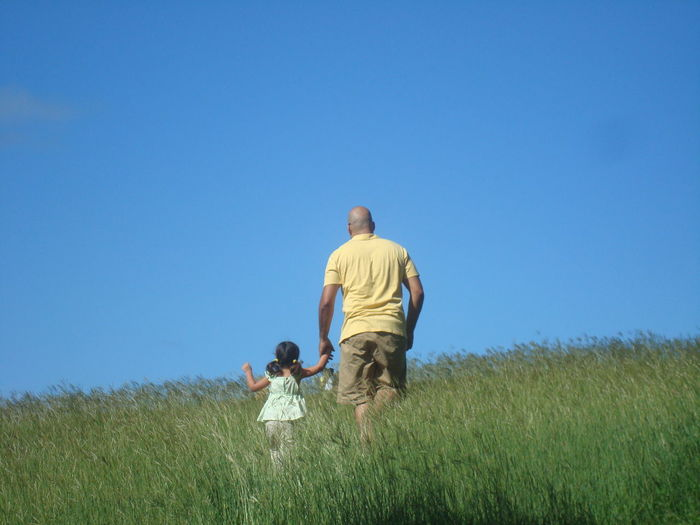 Rear View Of Father And Daughter Walking On Field Against Clear Sky
