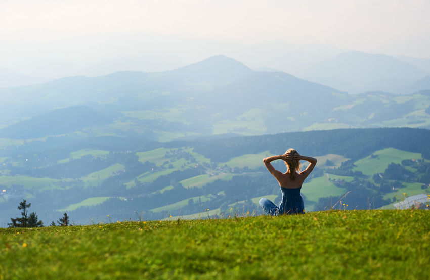 Woman sitting on mountain top. Austria Austria Europe Green Lawn Harmony High Hills Landscape Lotus Pose Meditate Meditation Mountain Peak Mountains Nature One Person Outdoors Peaceful People Relaxation Serene People Summer Sunny Day Travel Valley Woman Yoga