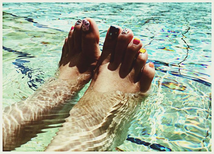 Close-up of bare feet in swimming pool