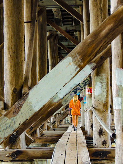 Girl under a bridge Architectural Column Architecture Beams Bridge Bridge - Man Made Structure Built Structure Clothing Connection Day Girl One Person Orange Color Outdoors Real People Rear View Structure Walking Wood Wood - Material 17.62° The Art Of Street Photography