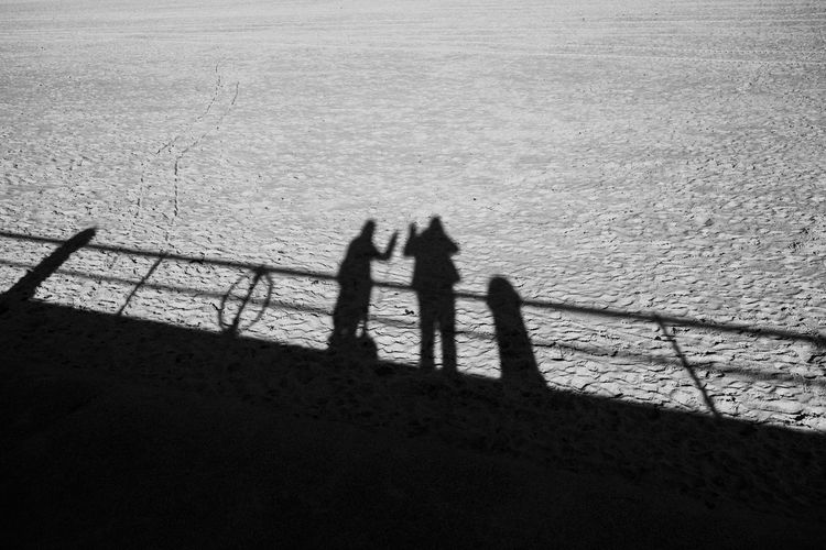 Shadow of people on sea shore