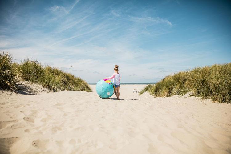 Full length of woman sitting on beach against sky