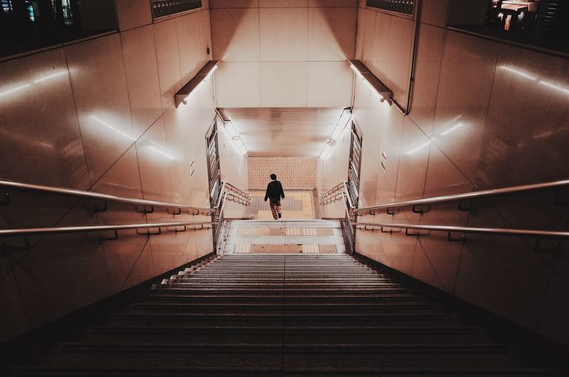 Loneliness Architecture Built Structure Ceiling Diminishing Perspective Direction Flooring Full Length Illuminated Indoors  Lifestyles Lighting Equipment Men One Person Railing Real People Rear View Staircase Steps And Staircases Subway The Way Forward Transportation Underground Walkway Underpass Walking The Street Photographer - 2018 EyeEm Awards