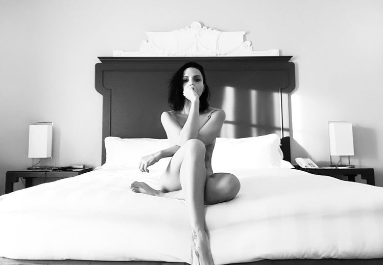 Full Length Of Naked Woman Sitting On Bed At Home