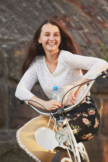 Portrait of smiling young woman sitting on bicycle