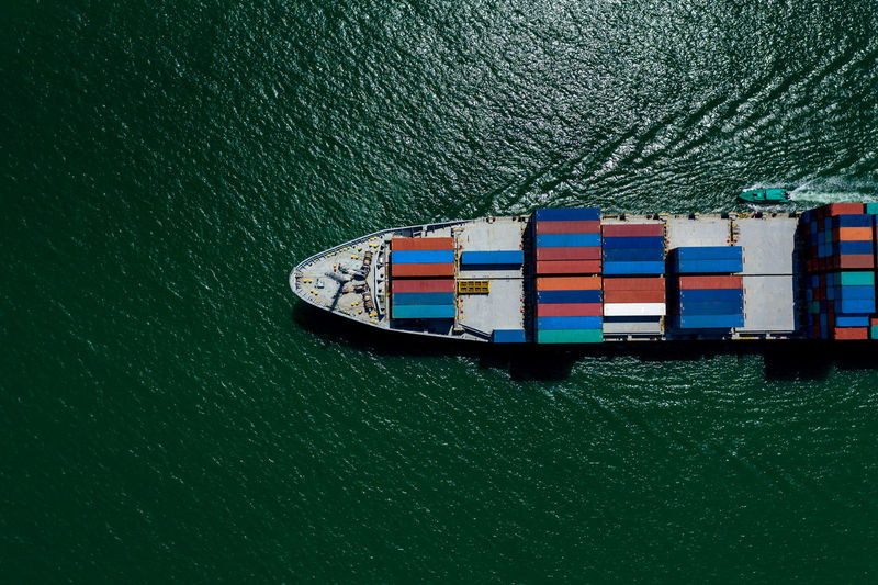 High angle view of shipping containers sailing on sea green