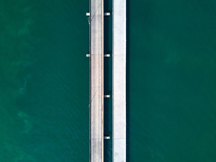 Aerial top view of a long highway bridge above a ocean. Vertical highway Water Built Structure Architecture High Angle View Blue Above Aerial View Bridge Bridge Over Water Construction Highway Expressway Bridge Transportation Transportation Building - Type Of Building Road River Sea Structure Concrete Green Drone  Droneshot Empty Road Freeway Nature