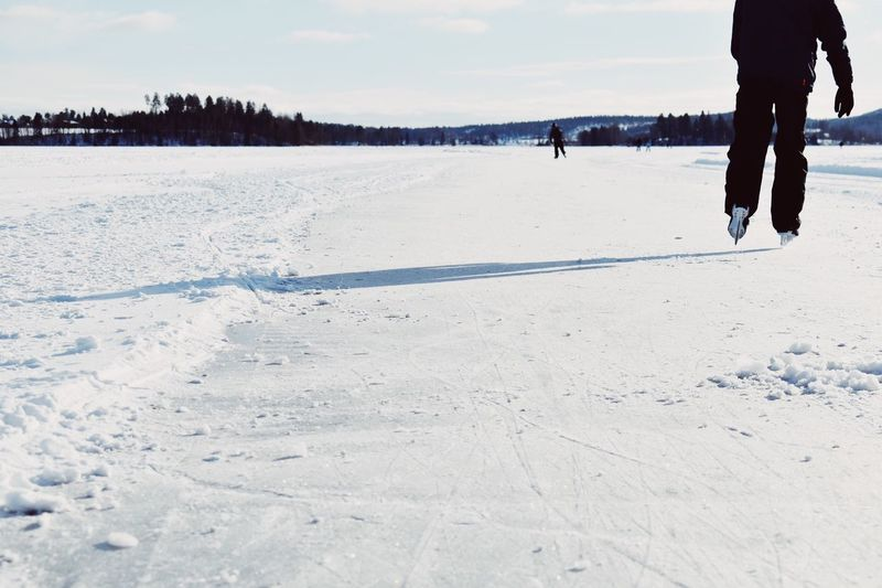 Low Section Of Man Ice Skating On Snowfield