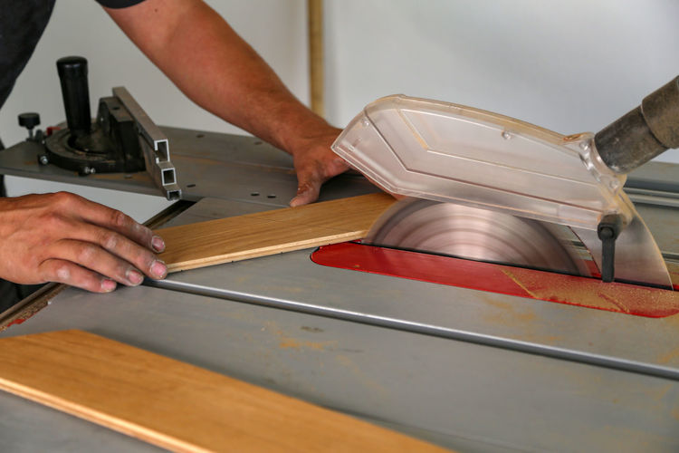Midsection of man cutting planks with saw