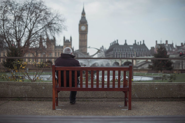 Man On Bench In City Against Sky