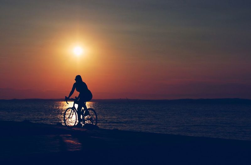 Silhouette woman riding bicycle at beach against sky during sunset