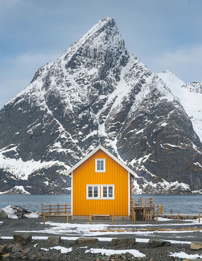 Yellow house against snowcapped mountain