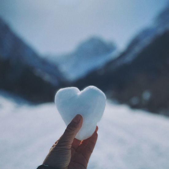 Close-up of hand holding heart shape during winter