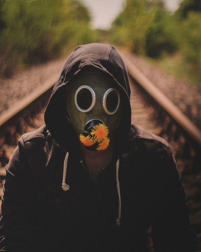 Portrait of person wearing mask on railroad track