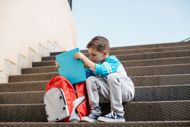 Boy putting book in bag while sitting on steps