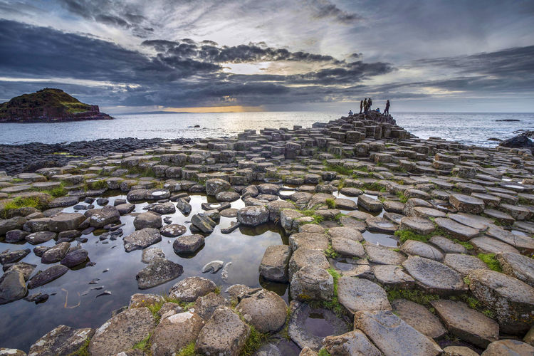Nature created a beautiful pattern of basalt columns at Giants Causeway, Northern Ireland Rock Group Of People Geological Formation Reflections In The Water Basalt Columns Unesco World Heritage GiantsCauseway Northern Ireland Outdoors Nature Land Horizon Scenics - Nature Horizon Over Water Travel Destinations Tranquil Scene Sunset Rock - Object Sea Cloud - Sky Water Tranquility Beauty In Nature EyeEmNewHere UNESCO World Heritage Site