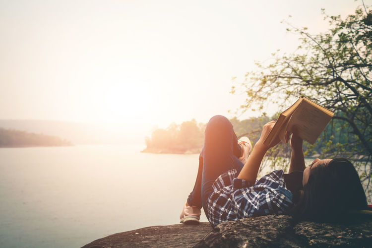 Woman reading book while lying on rock against lake