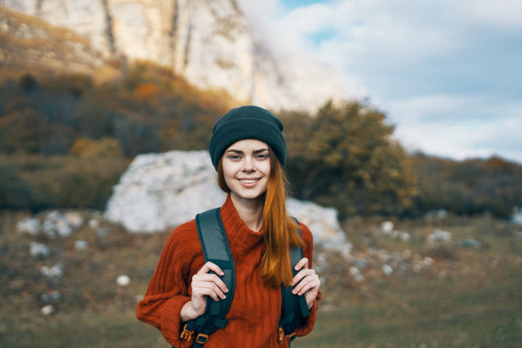 Portrait of smiling young woman standing in park during winter