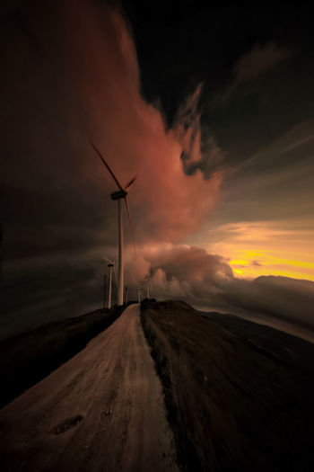 Wind turbine against sky during sunset