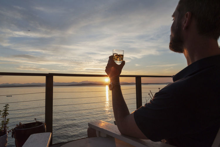 Rear view of a man drinking water at sunset