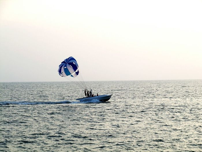 People Paragliding In Sea Against Clear Sky