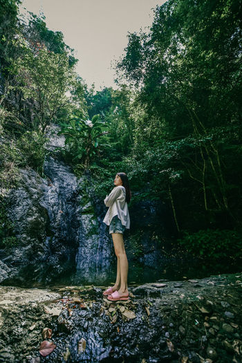 Full length of young woman standing on rock in forest