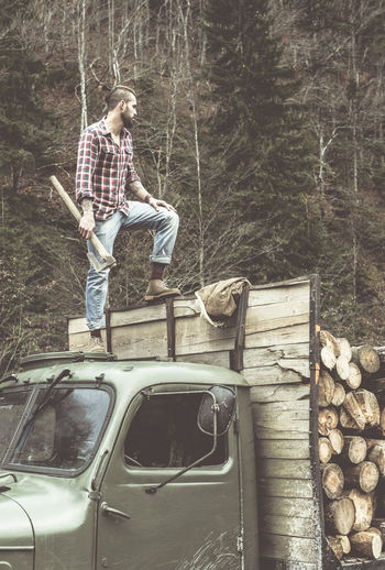 Young man standing on truck with stack of wooden logs
