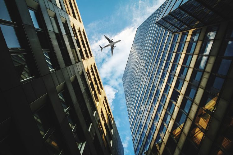 Low Angle View Of Airplane Flying Over Modern Buildings Against Sky