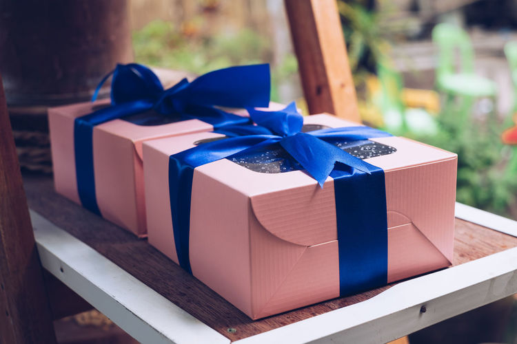 gifts Blue Bow Ribbon Ribbon - Sewing Item Box Gift Tied Bow Box - Container Container Gift Box Still Life Close-up Paper Focus On Foreground No People Celebration Surprise Wrapped Table Purple Backgrounds Object Peach Christmas Birthday Holiday Moments