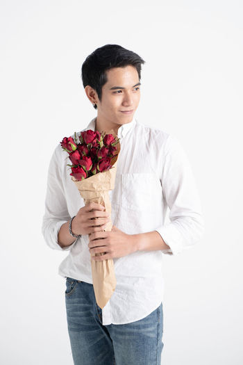 portrait of a young handsome man carrying a flower bouquet and ready to meet his date Front View Standing One Person White Background Three Quarter Length Holding Casual Clothing Young Men Young Adult Studio Shot Flowering Plant Flower Cut Out Indoors  Lifestyles Looking At Camera Portrait Smiling Bouquet