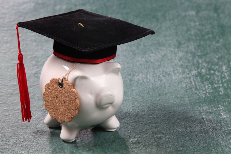 Mortarboard on piggy bank over table